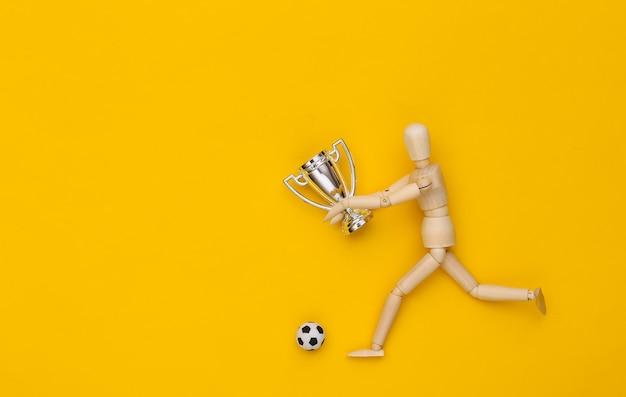 Houten marionet loopt met voetbal en kampioenschapsbeker op gele achtergrond
