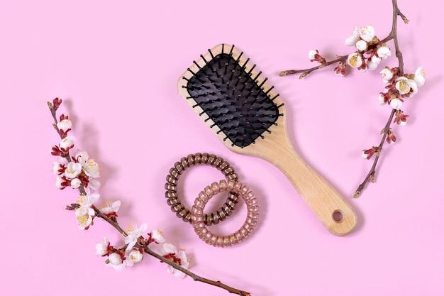 Houten massageborstel, haarspiralen en bloeiende abrikozentakken op roze achtergrond. concept van vrouwelijke schoonheid. haarverzorging thuis.
