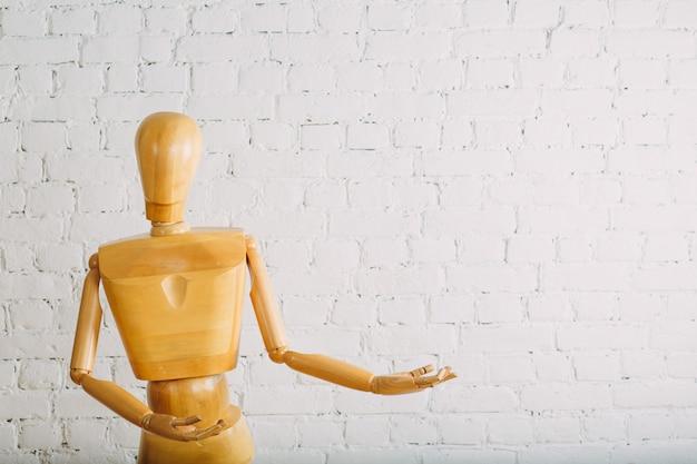 Houten mens op witte bakstenen muur met exemplaarruimte