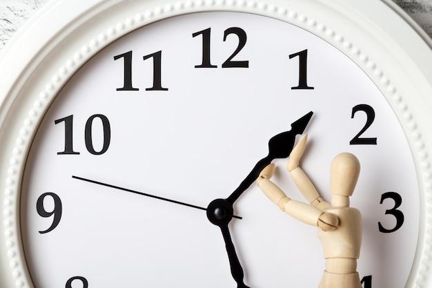 Houten menselijk cijfer dat de pijl van de klok probeert tegen te houden