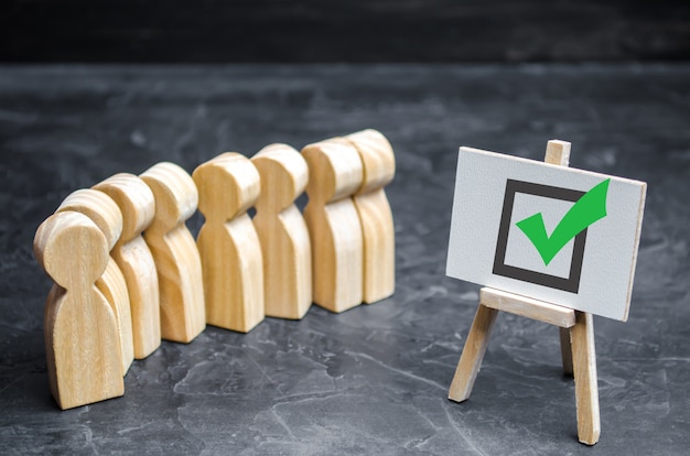 Houten menselijke figuren staan samen naast een vinkje in de doos. het concept van verkiezingen