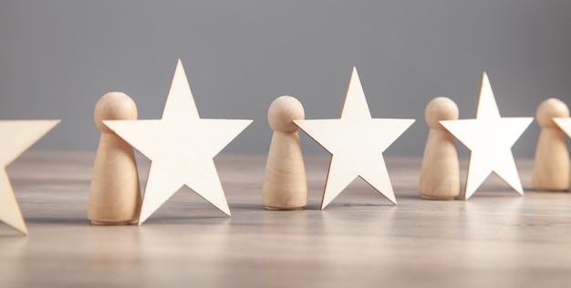 Houten mensfiguren met sterren. beste klantevaluatie en tevredenheid