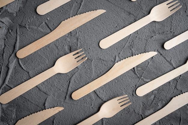 Houten mes en vork op de zwarte achtergrond. eco-vriendelijk concept zonder afval. bovenaanzicht met ruimte voor tekst. kopieer ruimte