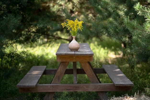 Houten meubels in de tuin buiten. eenvoudige banken en eettafel met boeket gele bloemen