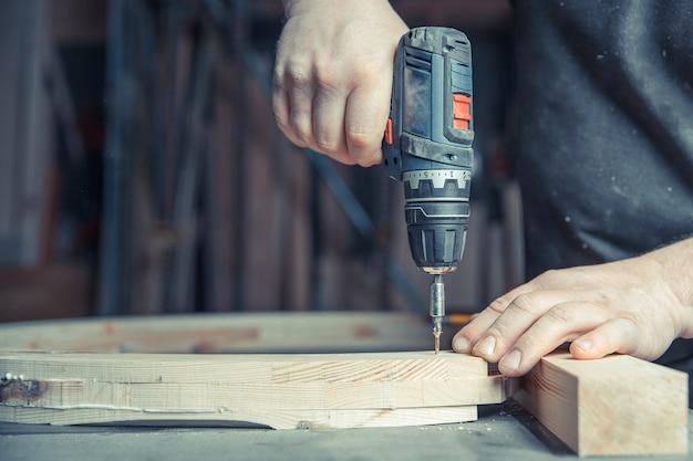 Houten meubels schroeven in een schrijnwerk met een elektrische boor