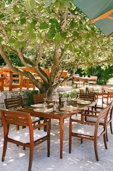 Houten meubilair in het restaurant buiten stoelen met witte kussens en tafels in hout voorbehouden