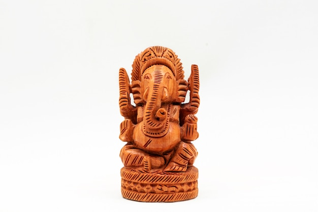 Houten miniatuur beeldje van de hindoe-god ganesha op een witte ondergrond