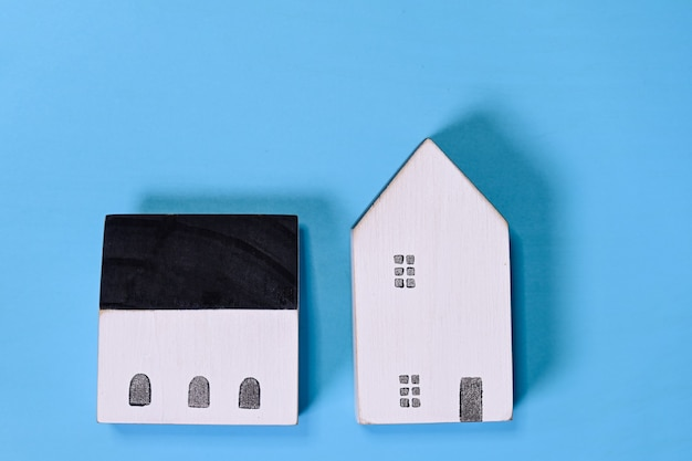 Houten miniatuurhuismodel op blauw symbool als achtergrond van nieuw huisconcept