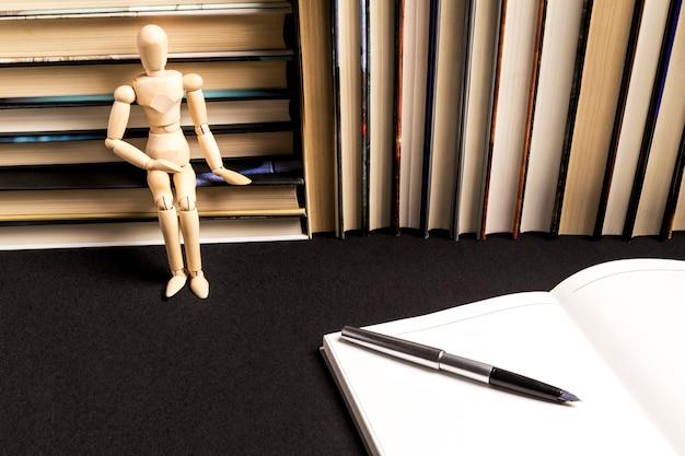 Houten model naast een pen op een leeg boek naast een boekachtergrond