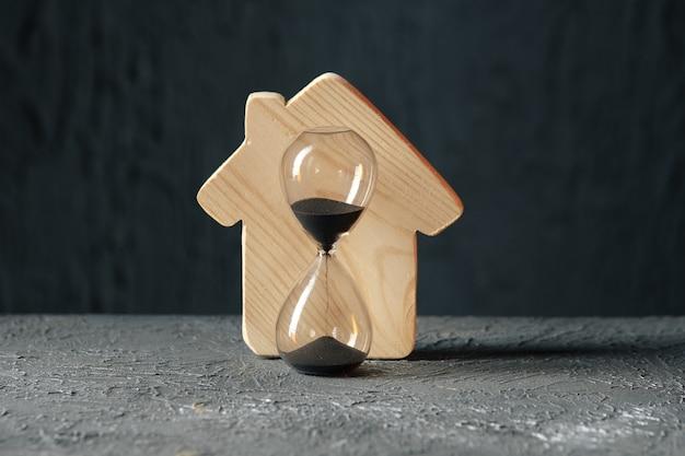 Houten model van huis en zandloper. een eigendomsconcept opslaan en kopen