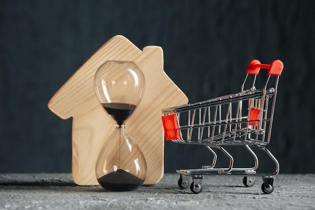 Houten model van huis, karretje en zandloper. een eigendomsconcept opslaan en kopen.