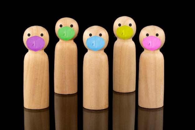 Houten modellen die apart staan en kleurrijke gezichtsmaskers dragen