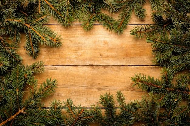 Houten muur met kerstboomtakken. kerstconcept. banier. ruimte kopiëren.