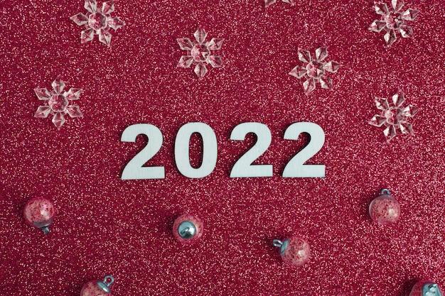 Houten nummers nieuwjaar met kerstdecor op glitter rode achtergrond