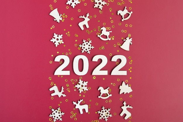 Houten nummers voor het nieuwe jaar 2022 met sterren en kerstdecor op rode achtergrond