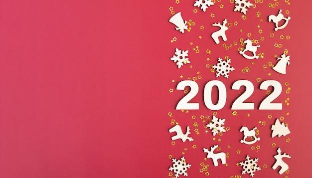 Houten nummers voor het nieuwe jaar met sterren en kerst decor op rode achtergrond met kopie ruimte banner...
