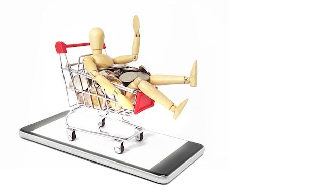 Houten oefenpop met zilveren munt in winkelwagen op mobiele telefoon geïsoleerd op een witte achtergrond. online winkelconcept.