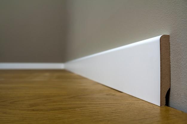 Houten of kunststof witte vloerplint installatie in grote lege ruimte op houten vloer en wit gestuukte stucwerk wanden. interieur details.