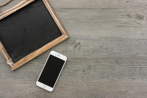 Houten oppervlak met een mobiele telefoon en schone lei