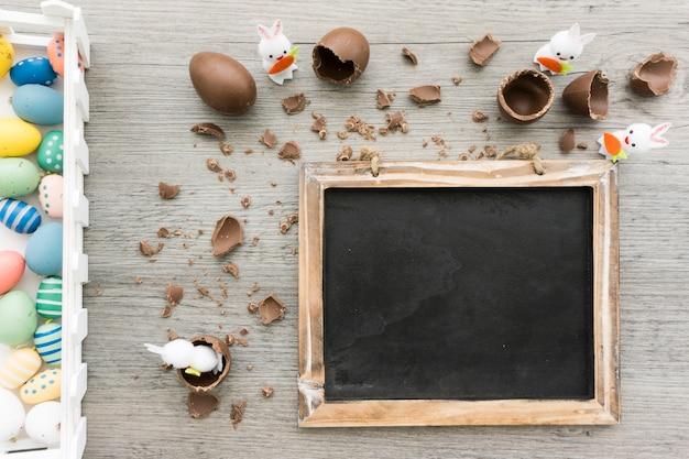 Houten oppervlak met leisteen, konijnen en chocolade-eieren voor pasen dag