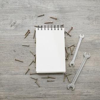 Houten oppervlak met notitieboekje, moersleutels en schroeven