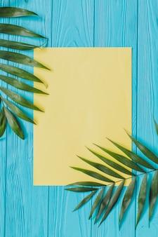 Houten oppervlak met papier en palmbladeren voor de zomer