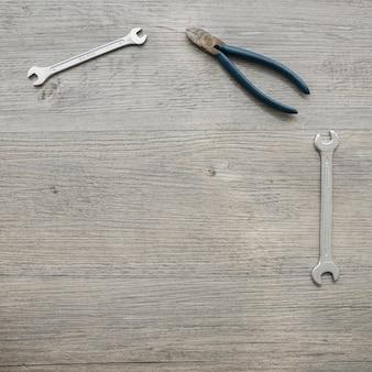 Houten oppervlak met tang en moersleutels