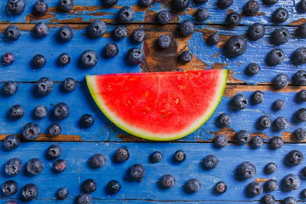 Houten oppervlak met watermeloen portie en bosbessen
