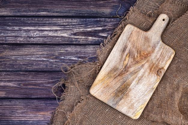 Houten oppervlak tafel met jute doek en snijplank