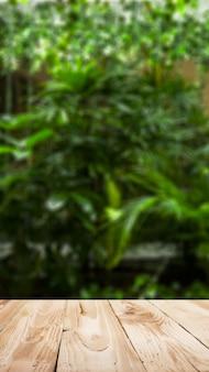 Houten oppervlak tegen de achtergrond van groene planten in de tuin in de middag