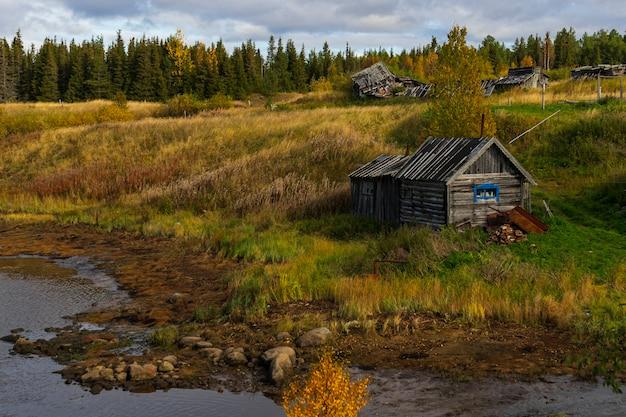 Houten oud huis aan de rivier, ver buiten de stad, regio moermansk in de herfst, landschap