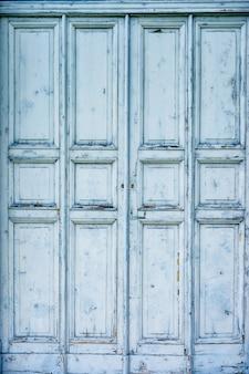 Houten oude deur van blauwe kleur met gebeeldhouwde rechthoeken en vierkanten