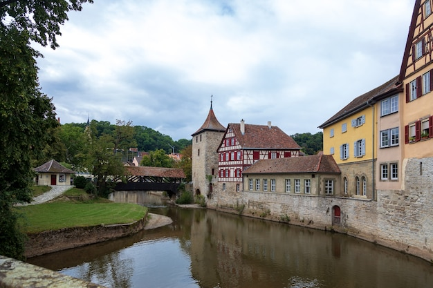 Houten overdekte brug en oude toren in het historische centrum van schw bisch hall aan de rivier de kocher, baden-württemberg, duitsland. zomer foto
