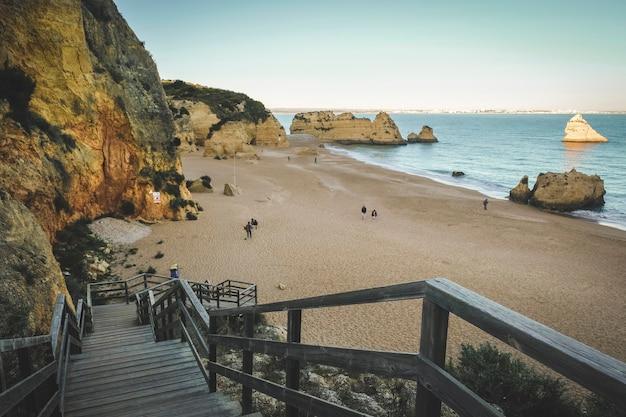Houten pad naar het strand van de atlantische oceaan in de stad lagos in portugal