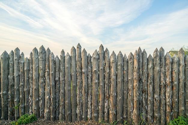 Houten palissade gemaakt van stammen. log houten hek. scherpe palen in de grond.