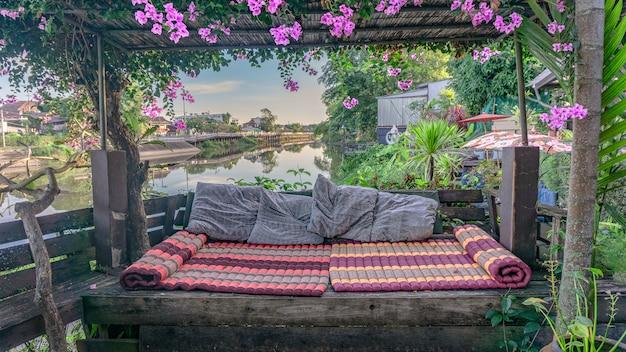 Houten pergora met klimop en matras-hoofdkussen bij rivieroever.