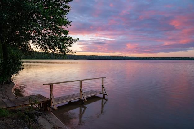Houten pier bij het meer met brandende zonsopganghemel en bos op de achtergrond.