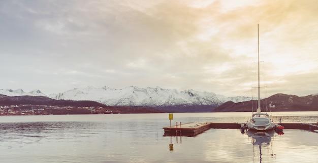 Houten pier en afgemeerd jacht. sereniteit en kalm landschap.