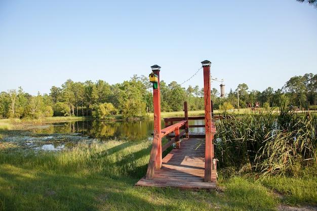 Houten pier om uit te rusten en te vissen in het dorp. heerlijke warme avond op het meer (vijver). mooie zomerse rustieke vijver.