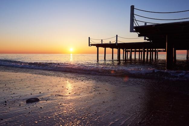 Houten pier op een mooie oranje zonsondergang.
