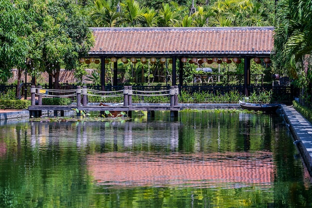 Houten pier op vijver in een tropische tuin in danang
