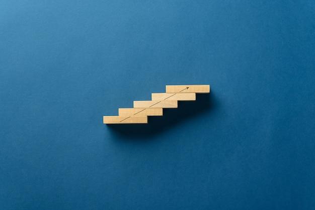 Houten pinnen geplaatst in een trapachtige structuur met een stijgende pijl erop getekend op blauw