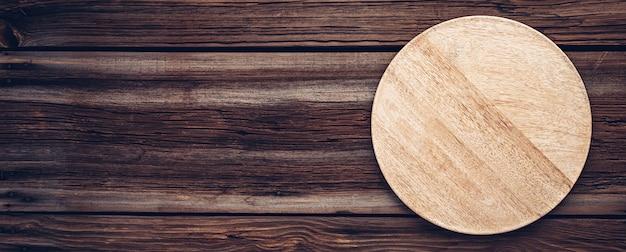 Houten pizzabord of bord voor eten op oude houten planken