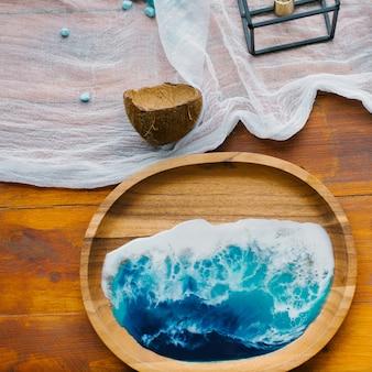 Houten plaat met epoxyhars in maritieme stijl in de vorm van zee of oceaan op de tafel