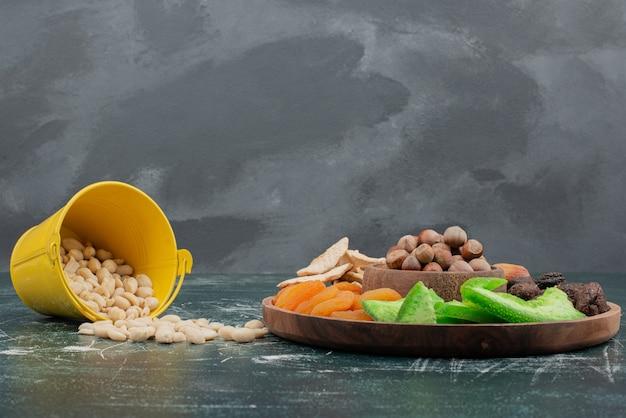 Houten plaat met gedroogd fruit en emmer met noten.