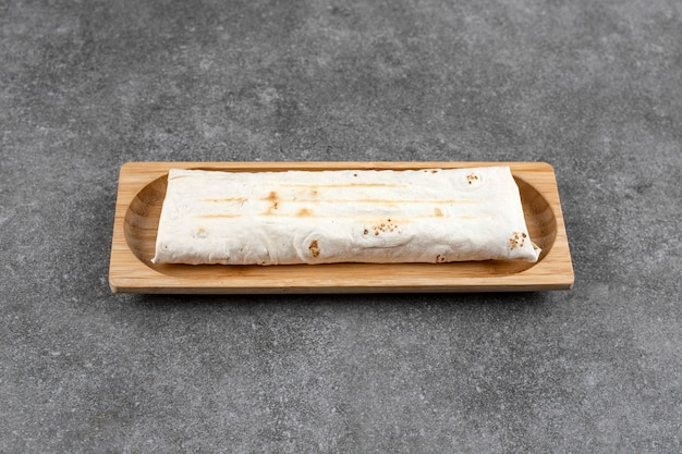 Houten plaat met gegrilde kip wrap sandwich op marmeren tafel.