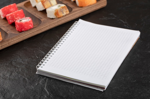 Houten plaat met traditionele sushibroodjes en notitieboekje op zwarte tafel
