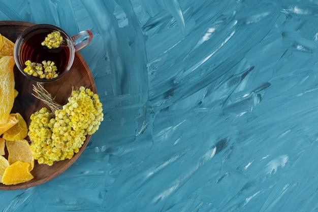 Houten plaat van gedroogd fruit en glas thee op blauwe achtergrond.
