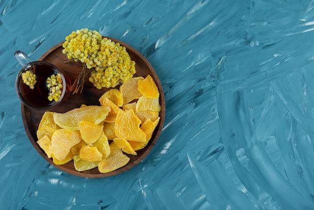 Houten plaat van gedroogd fruit en glas thee op blauwe ondergrond.