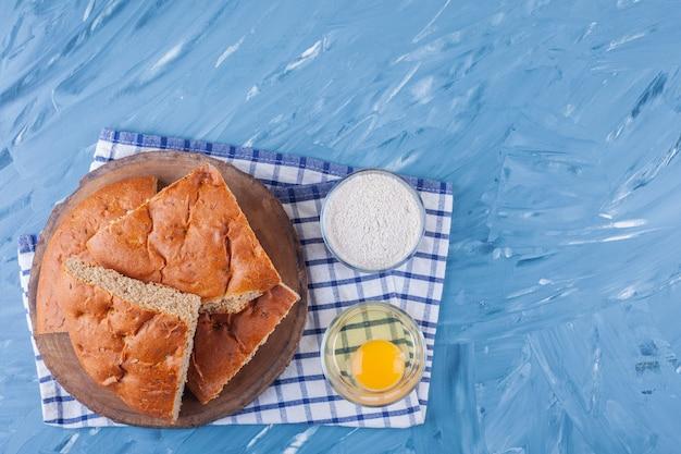 Houten plaat van gesneden brood, eigeel en bloem op blauwe oppervlakte.